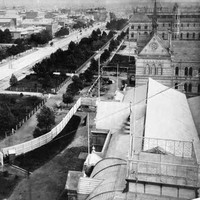 Image: Black and white photograph of a tree lined boulevard, as viewed from the roof of a building. The buildings lining one side of the road are grand stone constructions and are surrounded by formal gardens.