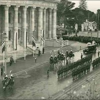 Image: lines of men in military uniforms plus others on horseback gather outside a large stone building with wide steps leading to its entrance and decorative columns along the entire facade.