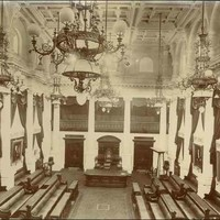 Image: a huge three storey high room with bench seating arranged in rows along the wall, facing inwards. There are long dark curtains draped above portraits, white columns along the walls, a decorative plaster ceiling and huge chandeliers