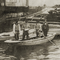 Image: Four men stand in a wooden row-boat next to landing steps on a riverbank. Two other empty row-boats are moored nearby, and a large building is visible on the shoreline in the immediate background