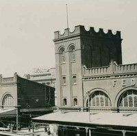 Image: Two large buildings with archway windows and a square-sided tower. Several cars of 1920s vintage are parked in front of the building