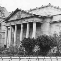 Image: A large, mostly windowless sandstone building fronted by a portico with six columns