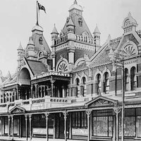 "Image: Black and white image of store front building with tiled roof, turreted towers and byzantine details. Sign reads ""Grants Coffee Palace"""