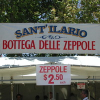 "Image: A group of people patronise a food concession housed in a white tent. A sign in Italian on the tent reads ""Sant' Ilario, Bottega Delle Zeppole"""