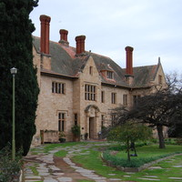 Image: Oblique view of the front of a large, two-storey stone mansion flanked by gardens
