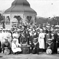 Men in naval uniforms plus the Burra girls and dignitaries group together for a photo infront of the local rotunda