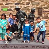 Image: children standing on sculpture