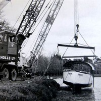 Image: boat being lifted from water by crane