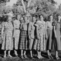 Image: Group of eight women standing in a line wearing long dresses
