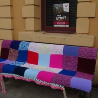 image: bench covered in knitting