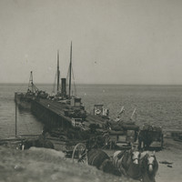 Image: A wooden jetty jutting out into the ocean with several horses and wagons and two large sail boats docked at the side