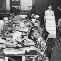 Image: A group of women sit on either side of a long table arranging paper documents, a man walks by with a trolley stacked with papers.