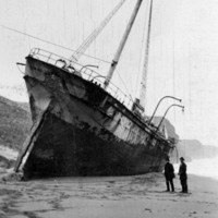 Image: A large sailing ship sits stranded on the beach, two men stand observing from the side