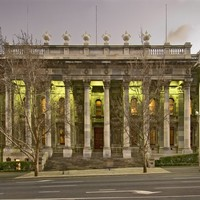 Image: a large stone building with two storey high columns along the entire facade, and wide stone steps leading up to its front entrance, is lit up with green lights at dusk.