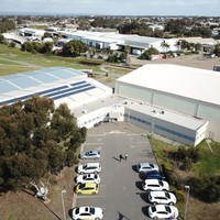 Image: aerial view of a group of hanger style buildings and car park