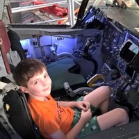 Image: young boy looking up from the cockpit of a plane