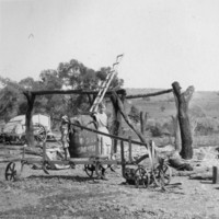 Image: Young boy standing outside among collection of farm machinery