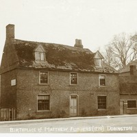 Birthplace of Matthew Flinders, Two storey brick house fronting a dirt road There is a window on either side of the front door, three upstairs windows, and two dormer windows in the roof, with slate roof. The house has since been demolished