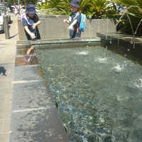 Two children standing next to a fountain