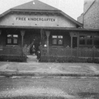 Image: two children standing in front of a cottage kindergarten