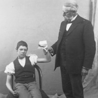 Image: seated boy with bandaged hand held by standing man