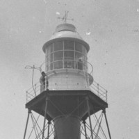 Image: A metal lighthouse stands on a desolate island. Two men stand in the lantern room at the top of the lighthouse, while a third sits outside the keepers' quarters at its base. A horse and cart stands next to the seated man