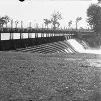 Image: A view a bridge over the river with water running down the steps located under the bridge