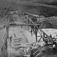 Image: Men working on structures over a flooding river