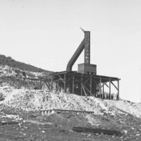 Image: A large chimney mounted on a wooden platform on the side of a hill. Several men stand at the base of the platform
