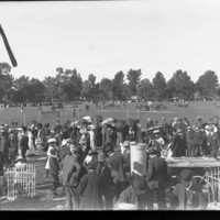 Image: A large group of people gathered on an oval with farm machinery on exhibition.