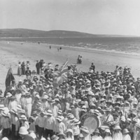 Image: Large group of children wearing hats on a beach with hills in the background