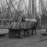 Image: Horse-drawn carts containing numerous large sacks of flour travel along a wharf next to a large, three-masted sailing ship