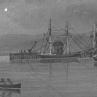 Image: A number of sailing ships are moored in a river. A scattering of buildings and a wharf are visible in the background