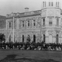Image: A large group of men dressed in late nineteenth century attire pose for a photograph in front of a large, two-storey stone building with a corner octagonal tower. A dirt street is visible between the photographer and the group of men