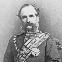 Image: A photographic portrait of a middle-aged Caucasian man in full military dress uniform. He has large mutton-chop sideburns and a bushy moustache
