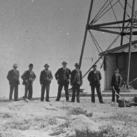 Image: A lighthouse stands at the top of a hill on a desolate island. A group of men in early Edwardian apparel pose for a photograph next to and in front of the lighthouse tower