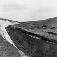 Image: Deep trench through a field with cows grazing on barehills in the background