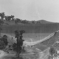 Image: A large concrete dam located among rolling hills looms behind a group of small timber buildings