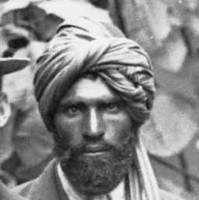 Image: Members of an exploring expedition pose for a photograph. An Afghan man with turban and western dress stands in the centre of the group