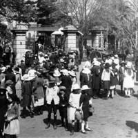 Image: crowd of children walking through large wrought iron gates