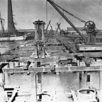 Image: The supporting framework of a bridge under construction extends across a river. Sailing ships, a wharf, and a large brick smokestack are visible in the image background