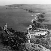 Image: Two women standing on rocks overlooking a rugged coastline