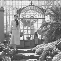Image: Two women in pale skirts and jackets over dark blouses stand apart from each other outside a large glass conservatory building in this posed black and white photograph from the 1930s.