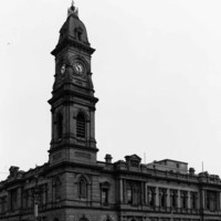Image: A large, two-storey stone building with a tall clock tower protruding from one corner. A street and sidewalk with people standing on it is visible in the foreground