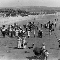 Image: People on a beach with houses and hills in the background.
