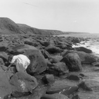 Image: View of a rocky coastline with a young girl clambering over rocks and cliffs in the background