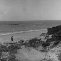 Image: Man on a beach with sand dunes in the foreground.