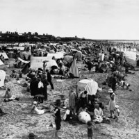 Image: Crowds of people on a beach with an assortment of tents