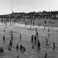 Image: View of beach with people bathing in the water and crowds on sand in the background