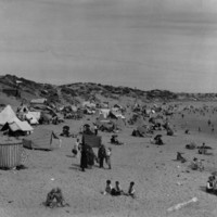 Image: People on a beach sheltering under umbrellas and tents